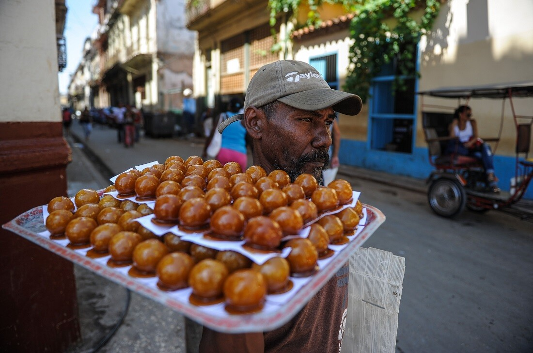 A man sells toffee coconuts in a street of Havana