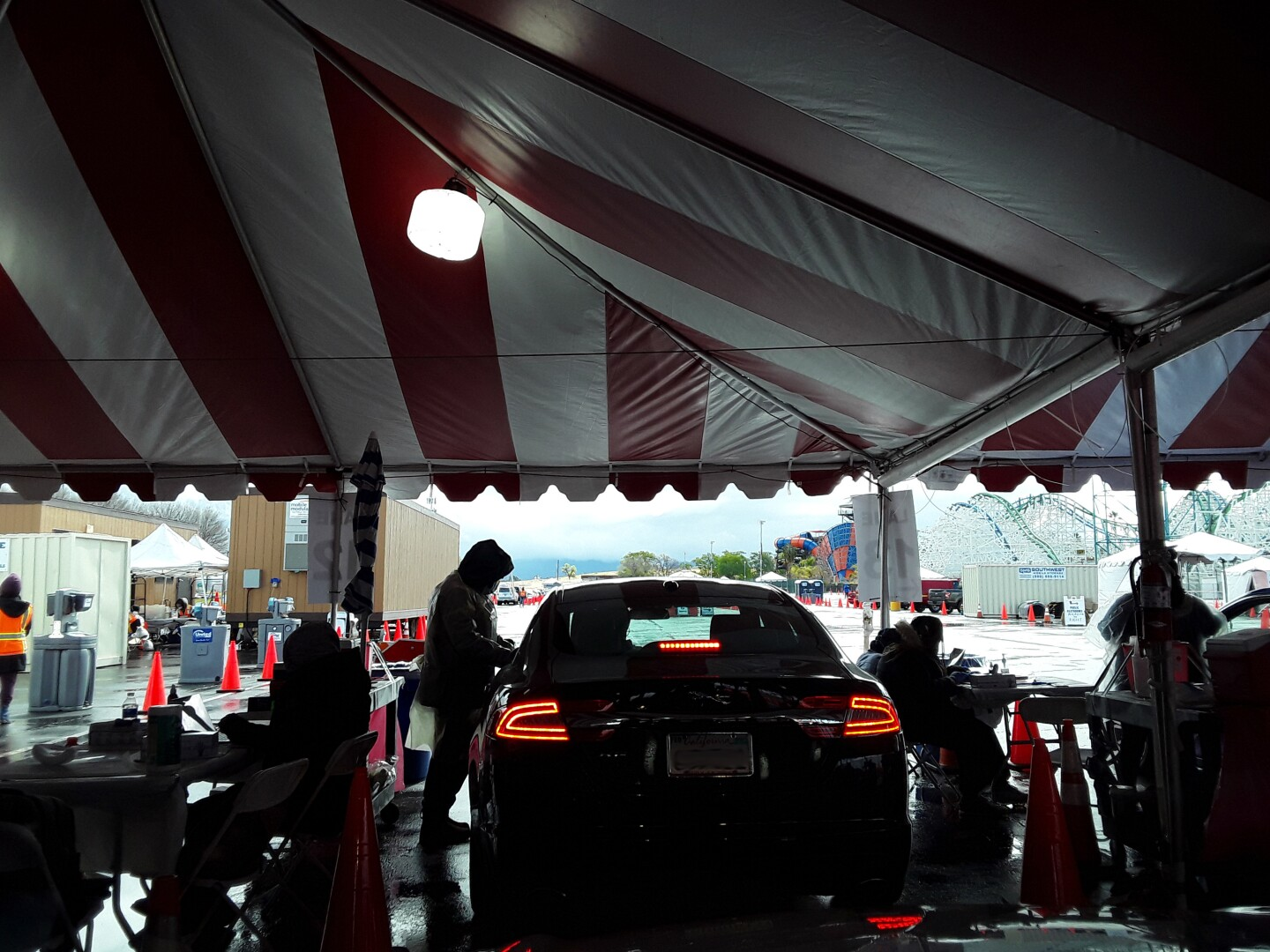 A car pulls into a tent as the driver preps to receive a dose of the vaccine in the parking lot of Six Flags Magic Mountain in Valencia, California.