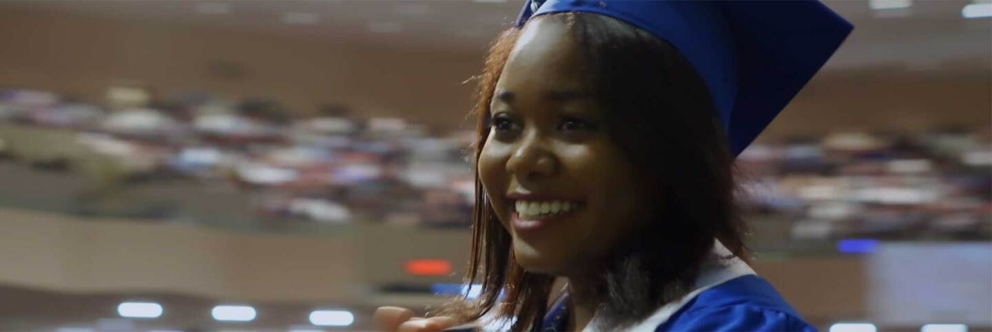 "op image is a still of Kierra Byrd, fellow in the Young Women's Advisory Council, receiving her college diploma. Still from the ""Global Mosaic"" episode ""Young Women Rising."""