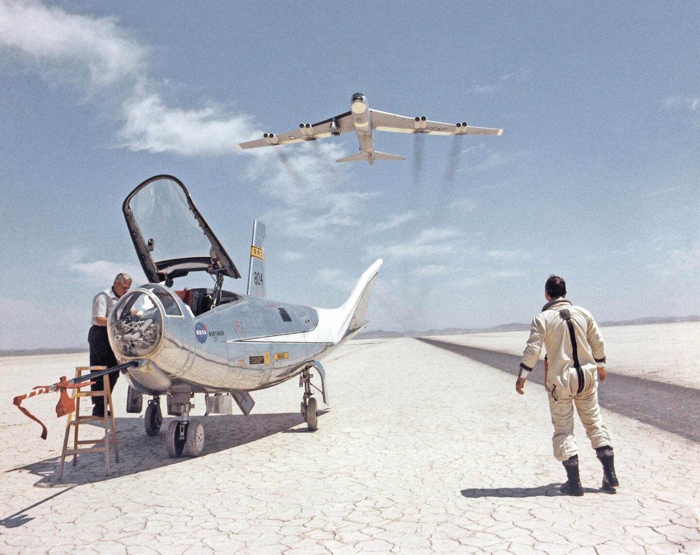 BLUE SKY METROPOLIS hero art. An HL-10 on dry lakebed with B-52 flyby, c. 1966 Courtesy, NASA (SERIES SIGNATURE IMAGE)