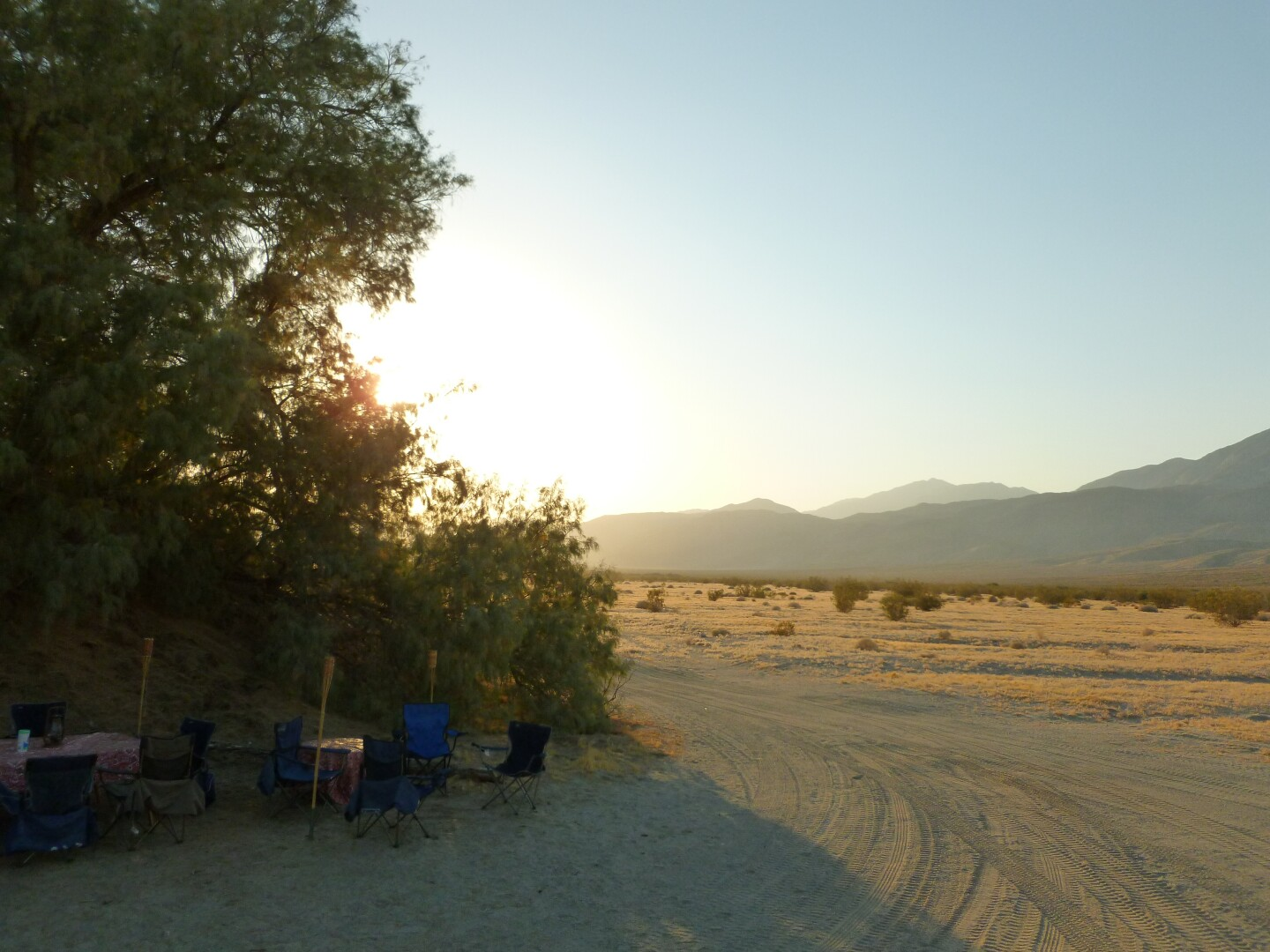 A roadside camp in a desert set up under some shade from local trees.