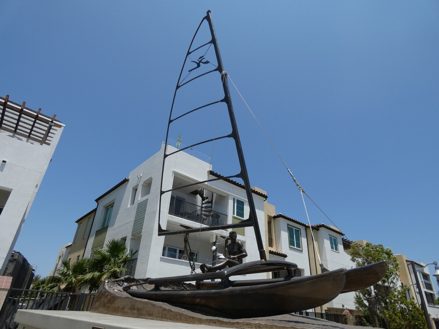 A bronze statue depicts surf and sailing pioneer Hobie Alter on a sail catamaran. Behind the sculpture are residential buildings.