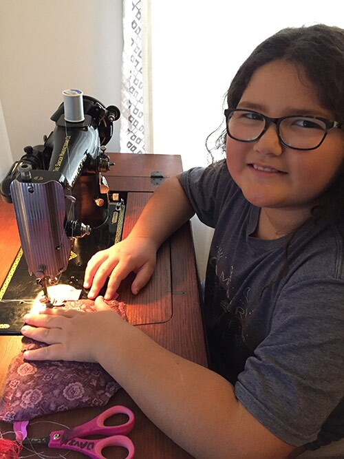 Eight-year-old Auntie Davina and the vintage sewing machine that she taught her mom, Gayle Isa, to use. | Photo by Gayle Isa /Courtesy of Auntie Sewing Squad