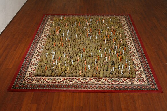"""Potatoes and Elk on an Imitation Persian Rug,"" 2010, installation of imitation Persian rug, potatoes, and plastic elk.  