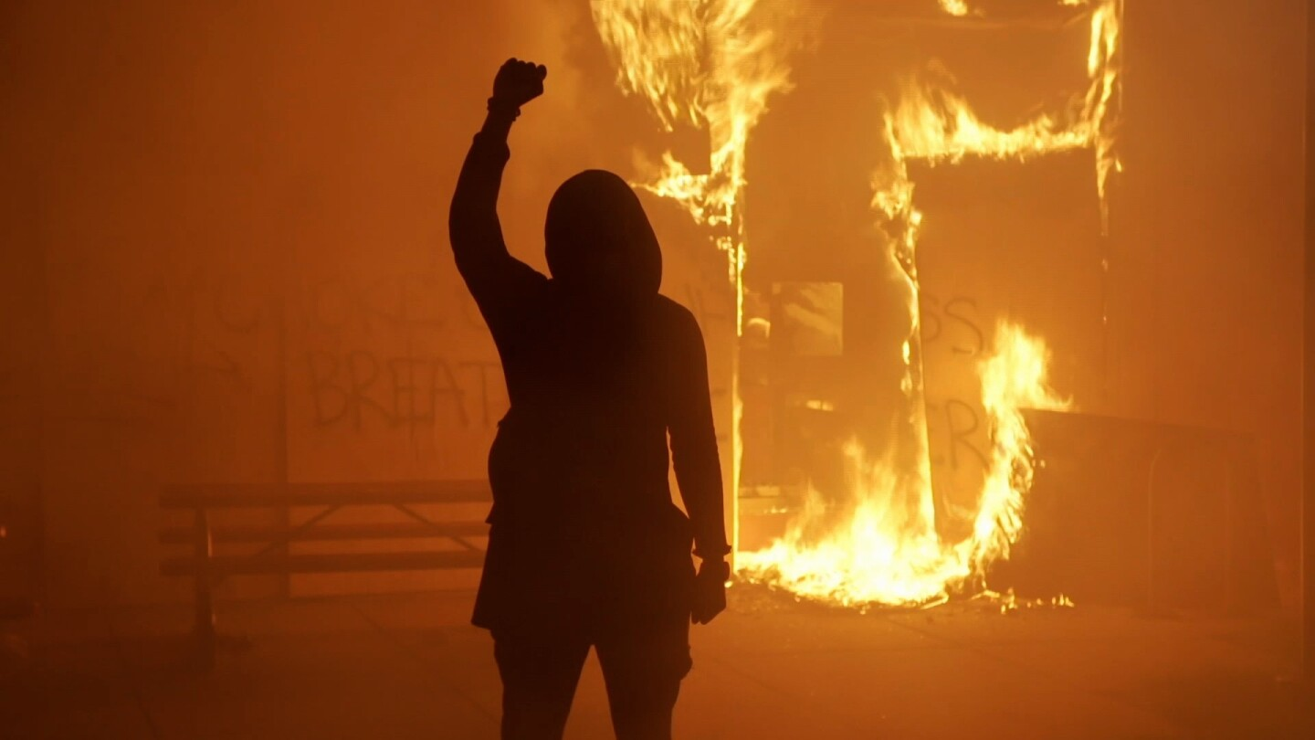 The silhouette of a person raising their fist as a building is on fire in the background.
