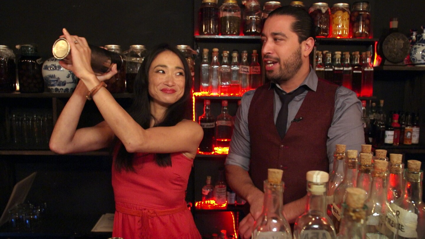 """Lucky Chow"" host Danielle Chang uses a cocktail shaker while a bartender standing beside her observes."