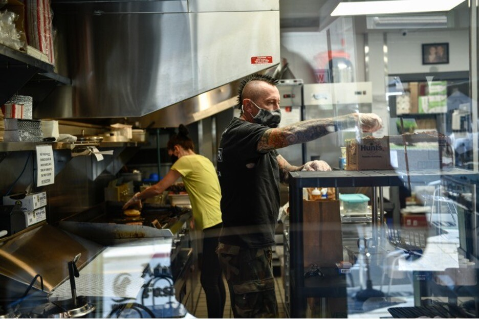 Alex Armstrong, 51 and his wife, Paula Armstrong, 45, prepare pick up orders during lunch hour at their Long Beach restaurant, VBurger.