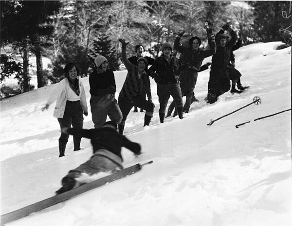 Group of people in winter gear smiling and waving while one of them falls down onto the snow at Big Pines. | Digitally reproduced by the USC Digital Library; From the California Historical Society Collection at the University of Southern California