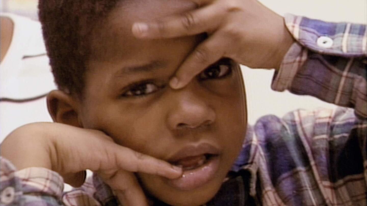 A child pressing his hands against his face as he looks into the camera.