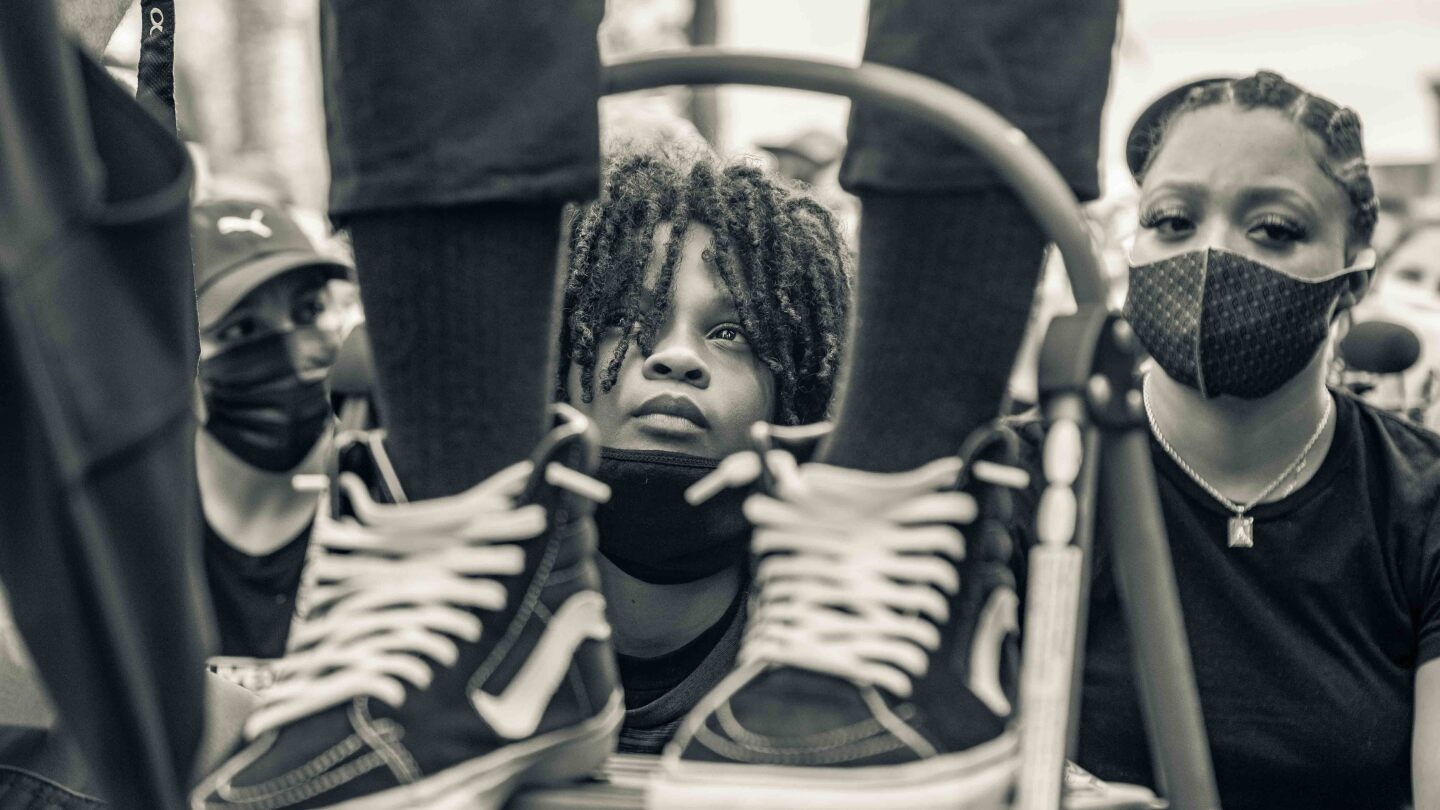 Kid looks up, framed between someone else's sneakers, at a George Floyd protest | Trevor Jackson