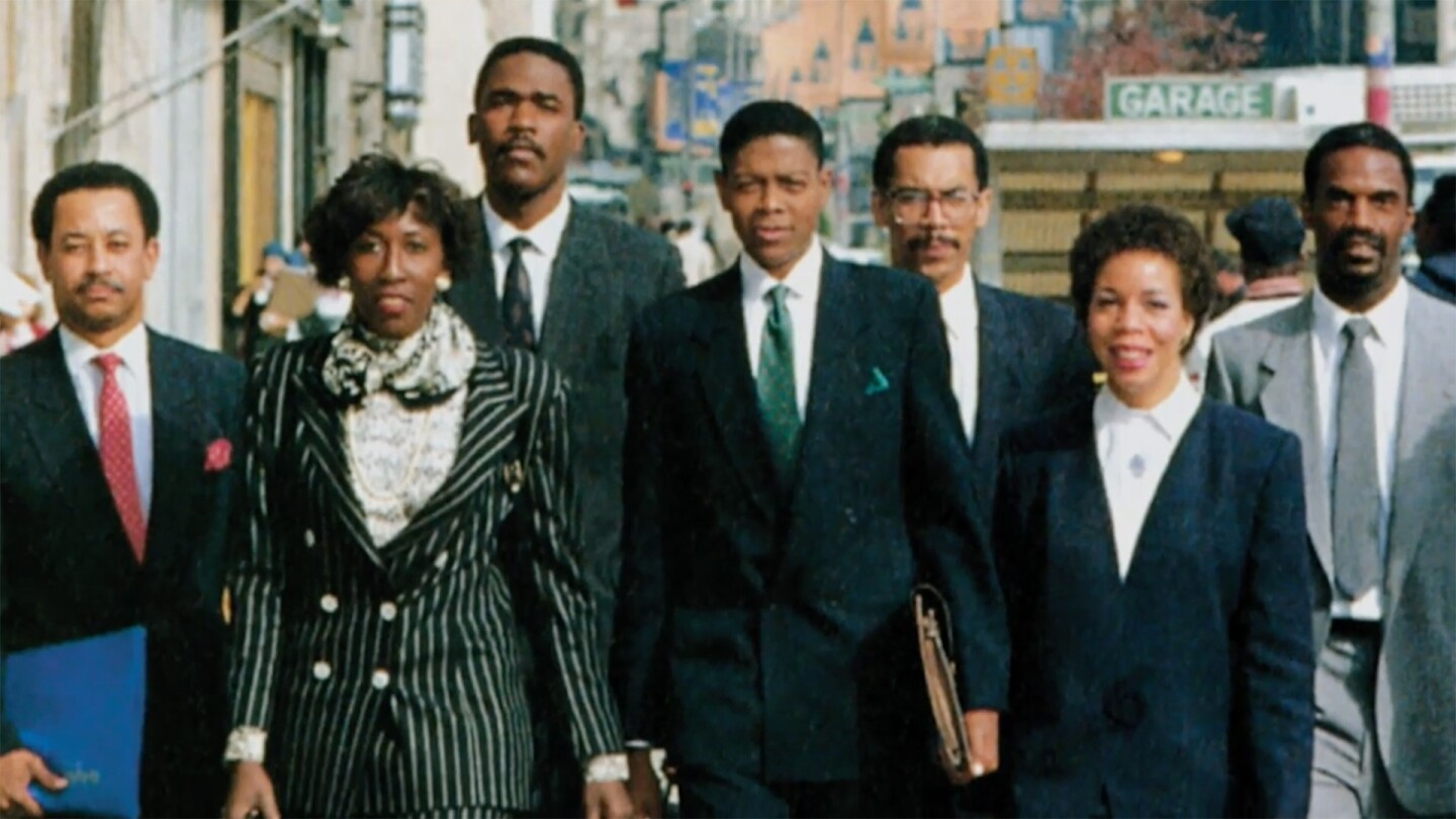 """A group of African American people wearing business attire walk together on a city street. 