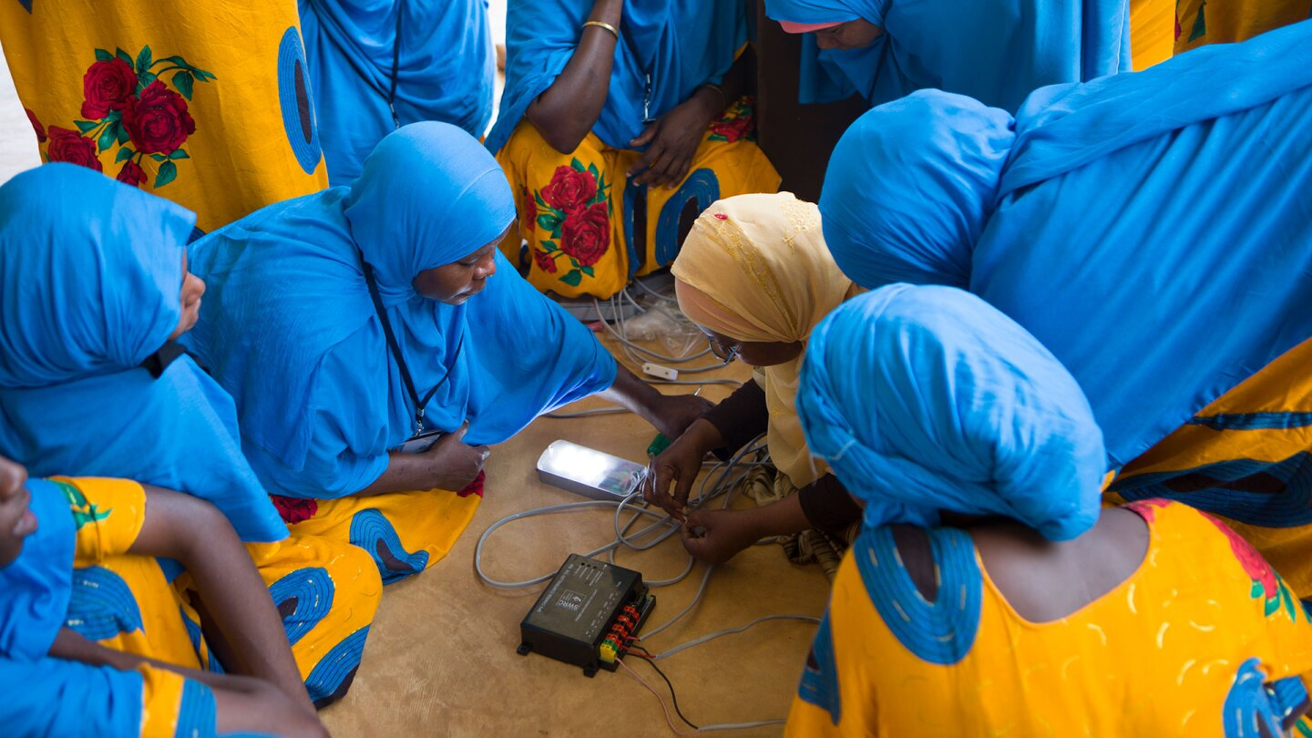 A group of women in Zanzibar studies solar installation. | Nicky Milne/Thomson Reuters Foundation