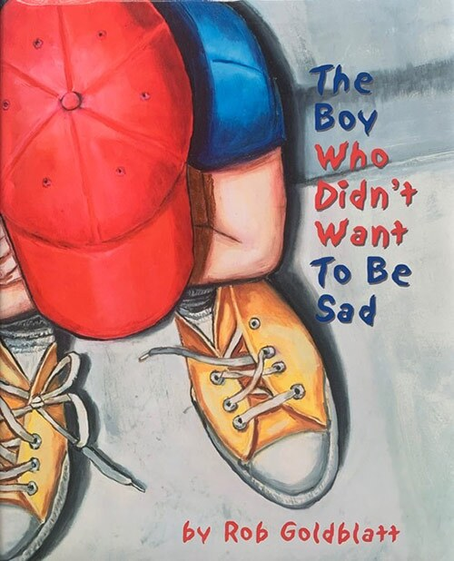 "Book cover of ""The Boy Who Didn't Want to Be Sad"" written and illustrated by Rob Goldblatt featuring an illustration of a little boy looking down at his sneakers. 