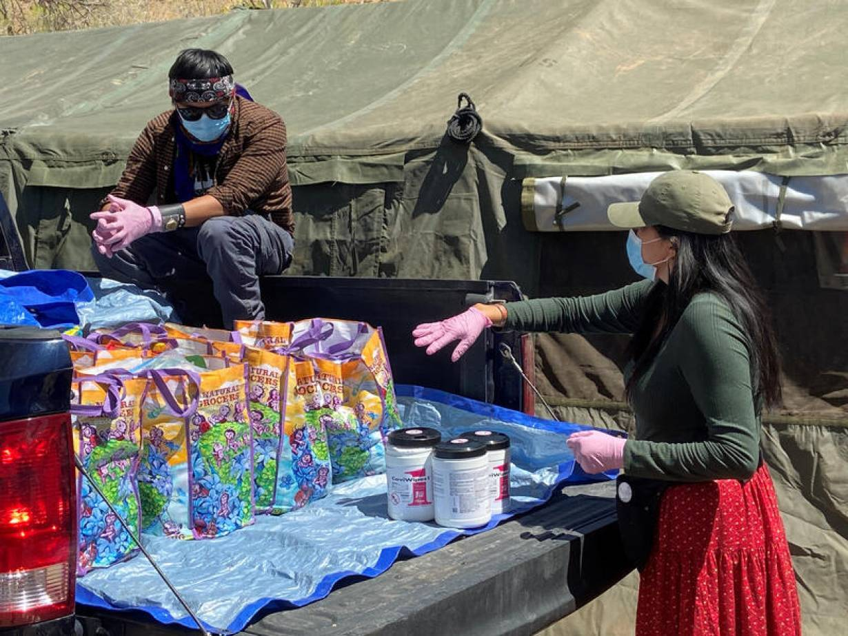 FILE PHOTO: A relief worker helps another volunteer load supplies into a pickup truck at a farm, used as a base for aid to Navajo families quarantined in their homes due to the coronavirus disease (COVID-19) in Hogback, Shiprock, New Mexico, U.S., April 7
