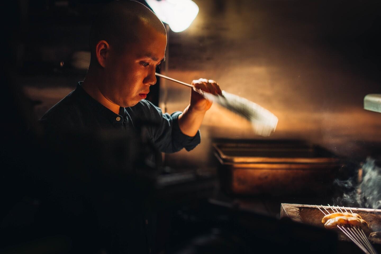 Chef Jon Yao prepares two bite-sized fish skewered over a smokey box.