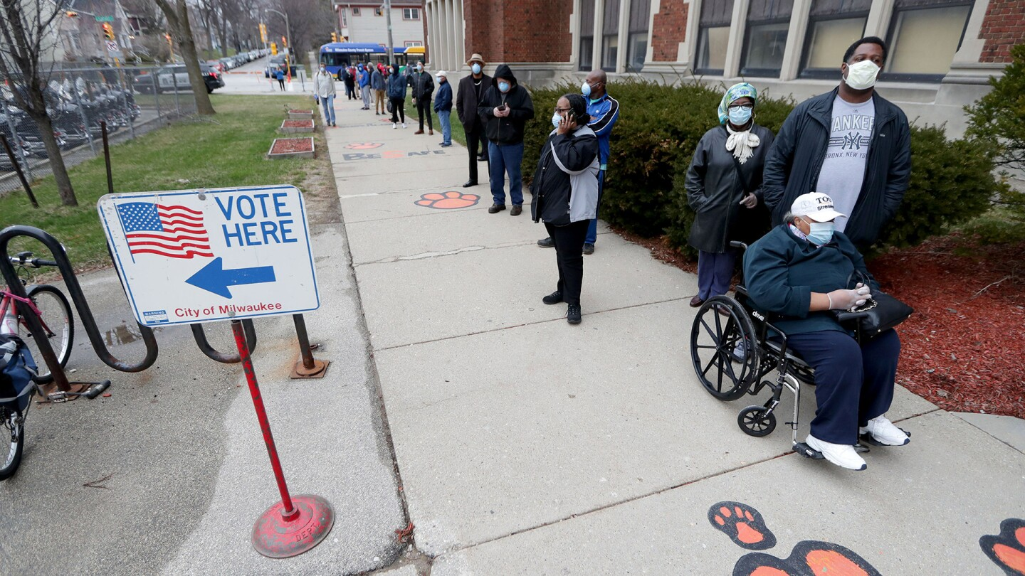 Amid the COVID-19 pandemic, residents of Milwaukee, Wisconsin wait in line to vote in the presidential primary election while wearing masks and practicing social distancing. April 7, 2020.