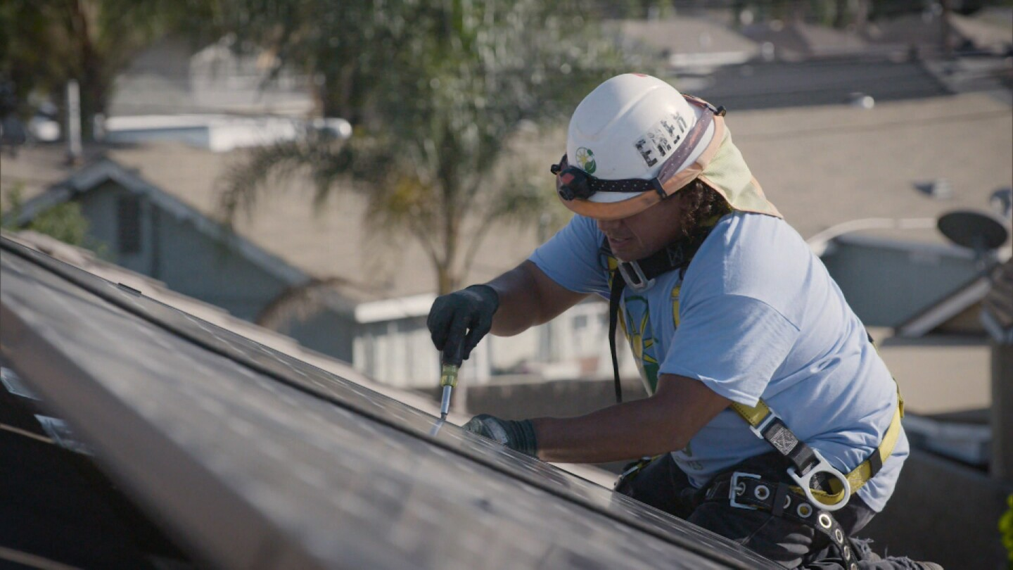 "A man installs a solar panel on a rooftop. | Still from ""Earth Focus"" episode ""Lighting a Path"""