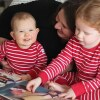 A woman cuddles two small children in matching pijamas as they read together on a bed.