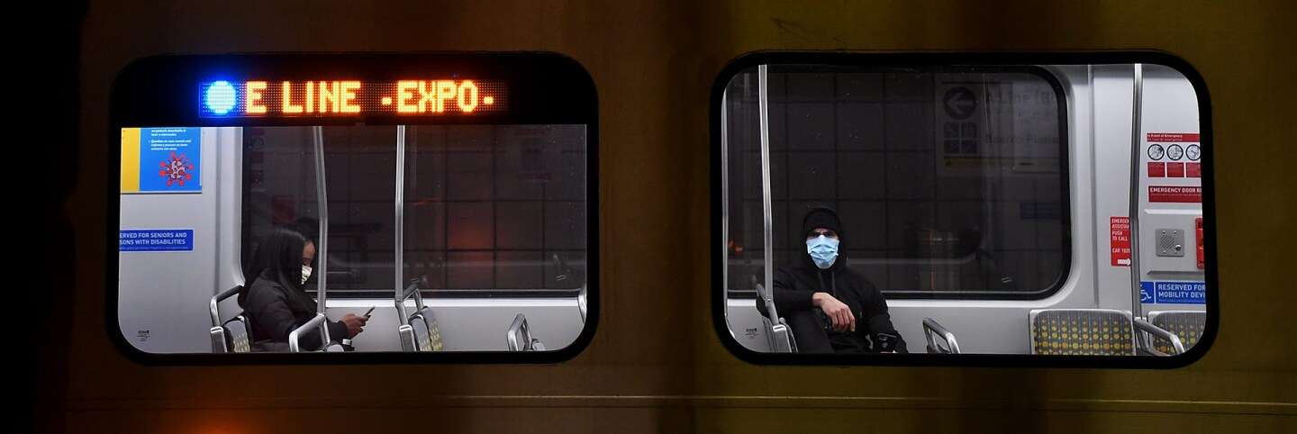 Passengers wear masks during a coronavirus breakout on the Metro train in Downtown Los Angeles. | Wally Skalij/Los Angeles Times via Getty Images