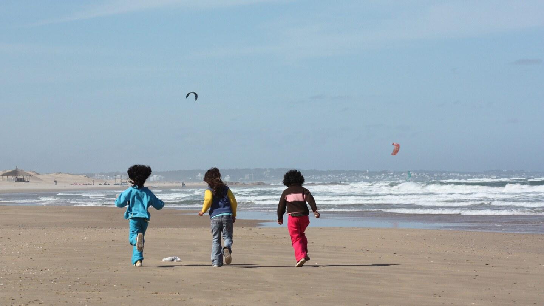 Tres niños corren en una playa