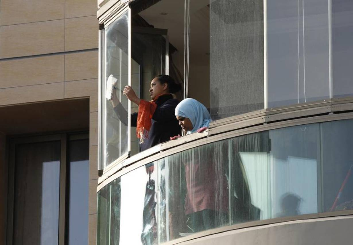 Housemaids clean windows in an apartment in Beirut April 2, 2012. Tragic tales of domestic worker abuse in Lebanon are common. | REUTERS/Jamal Saidi