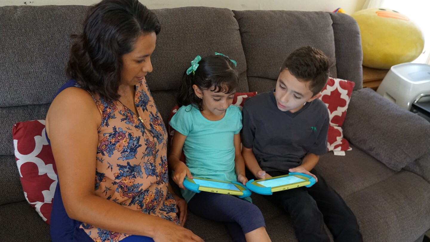 A mother and 2 young children using mobile devices. | PBS SoCal