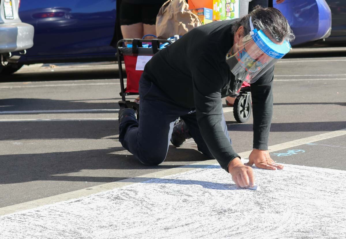 Protestor drawing with chalk during Immigrant Detention Day of Action (Alfombra Centroamericana) organized by the coalition of Central American organizations.| Nelson Lemus, In Plain Sight