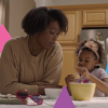 A small child counts out the corners of a triangular chip as her mom looks on
