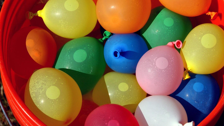 Una canasta llena de globos de agua de muchos colores.