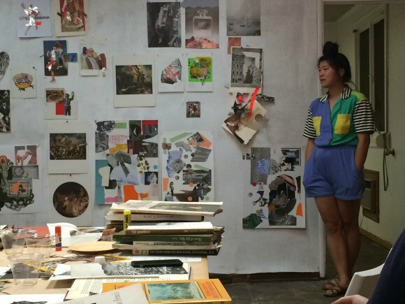 Soyoung Shin, a participant in the Collage Night workshop at the Women's Center For Creative Work, stands by the collages during the end of the night critique. | Photo: Robby Herbst.