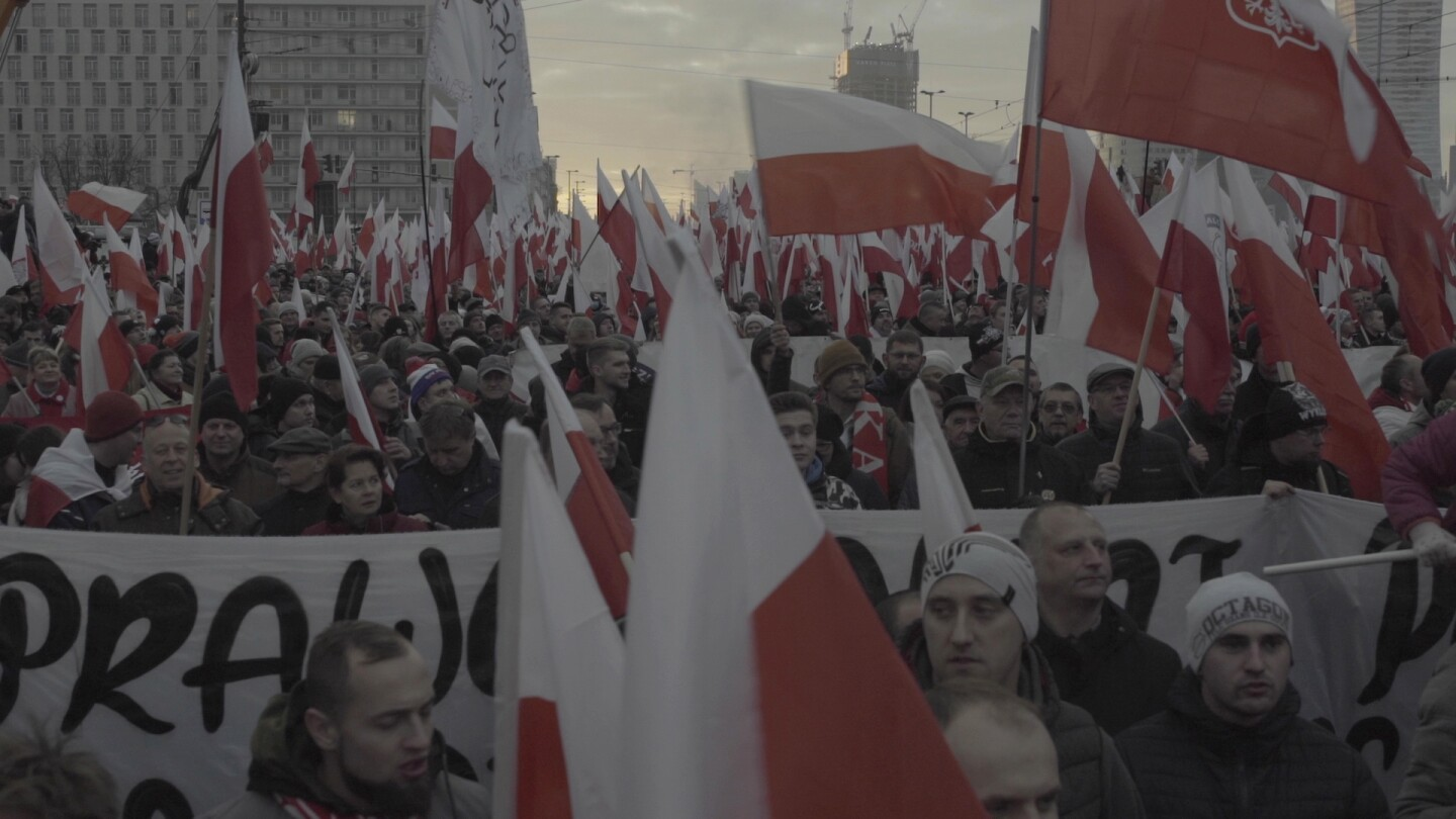 "A sea of demonstrators hold up Polish flags in a mass protest. | From ""Foreign Correspondent: A New Crusade"""
