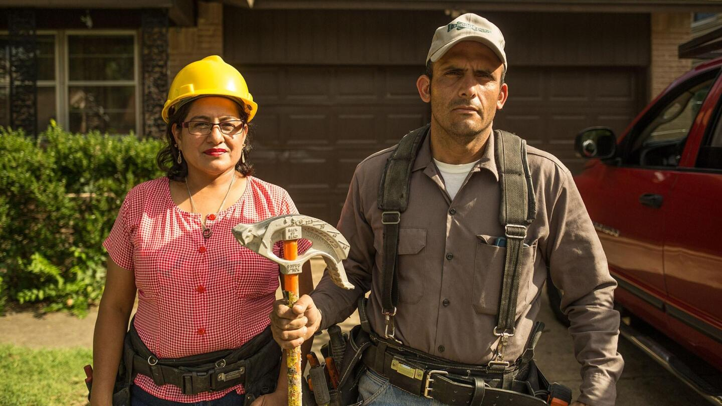 """Two workers stand side by side, one of them holding a construction tool. 