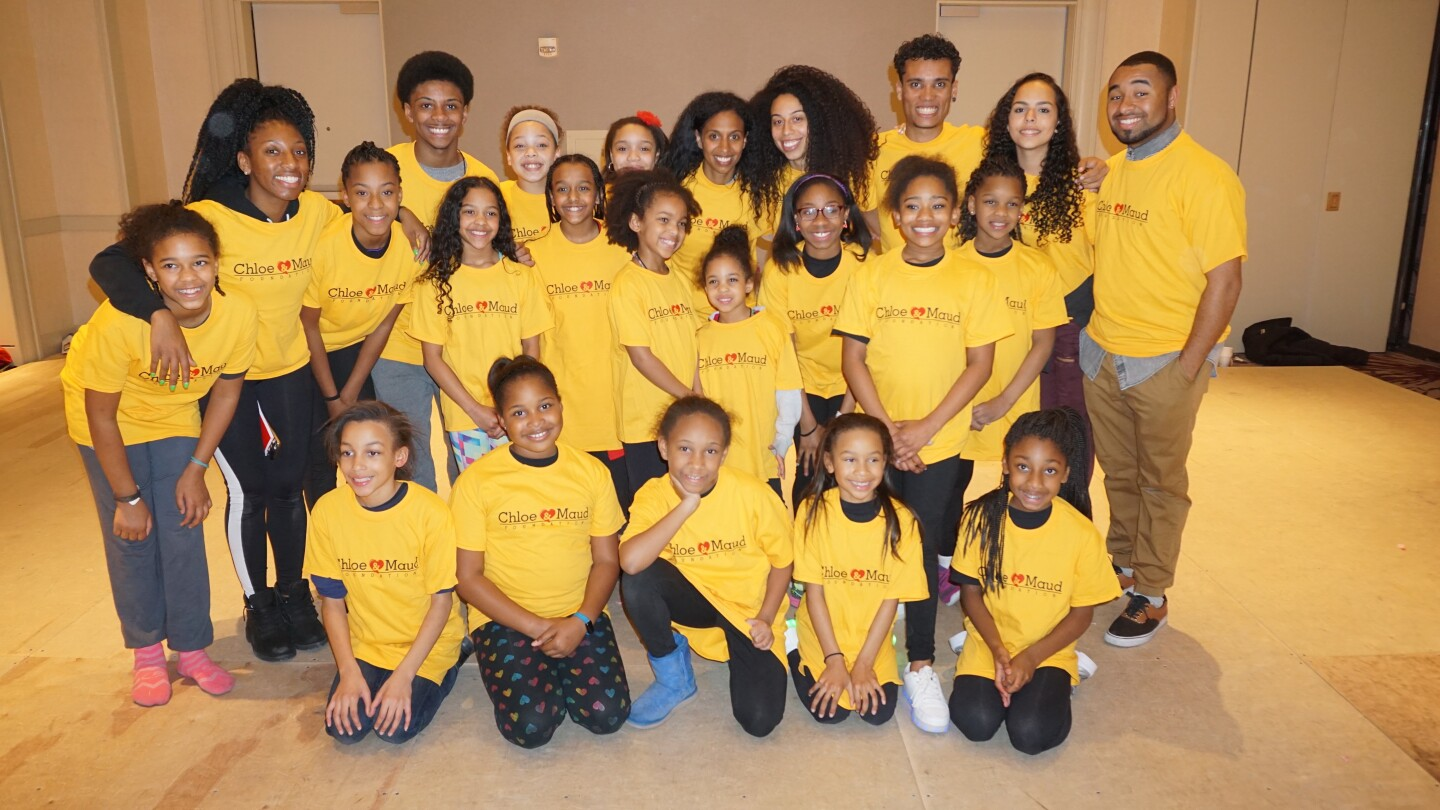 Students and faculty of Chloe and Maud Foundation wearing yellow pose together for a photo.