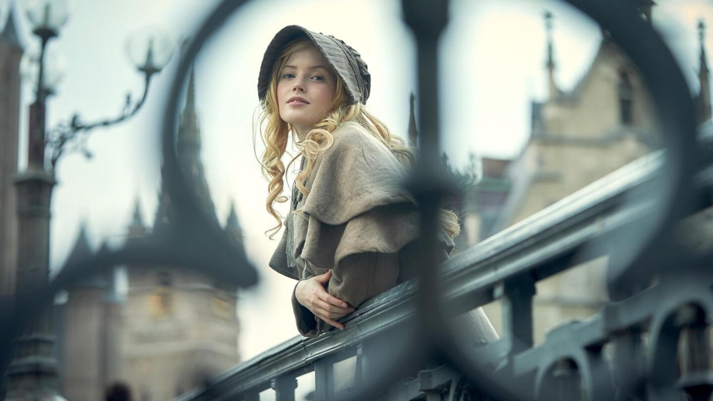 "Ellie Bamber as an older Cosette leans over a railing in Paris. | From ""Les Miserables On Masterpiece"""