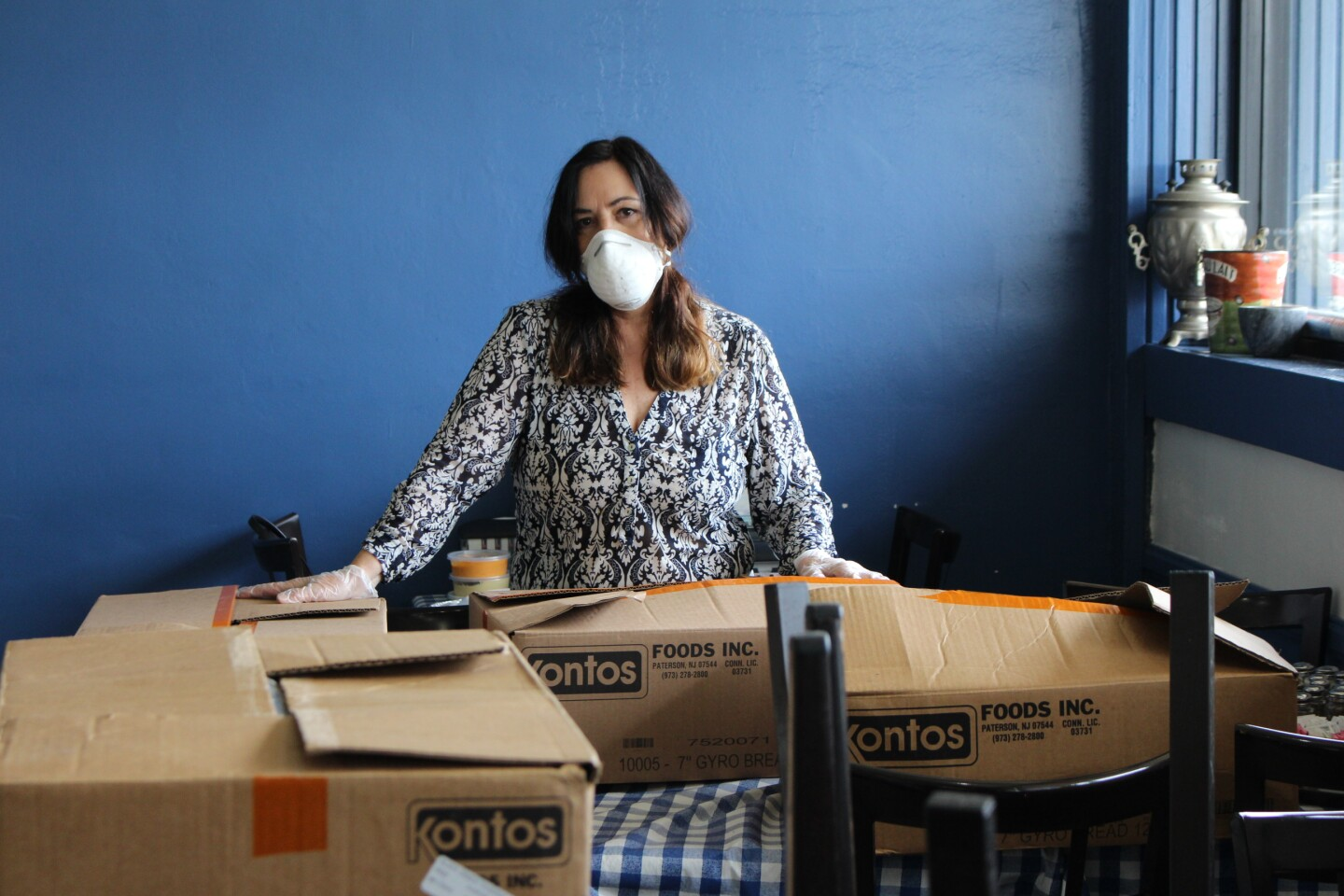 Woman with mask on posing with boxes of food for healthcare workers during COVID-19 outbreak