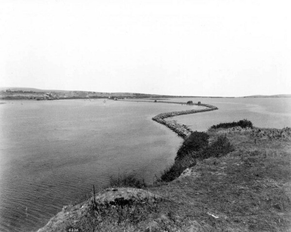 Circa 1900 view from the top of Dead Man's Island, showing  Rattlesnake (Terminal) Island in the distance and the long jetty that connected the two landforms. Courtesy of the USC Libraries - California Historical Society Collection.