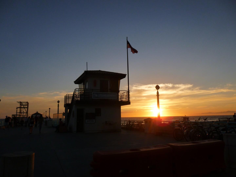 A lifeguard station at Manhattan Beach Pier during sunset.