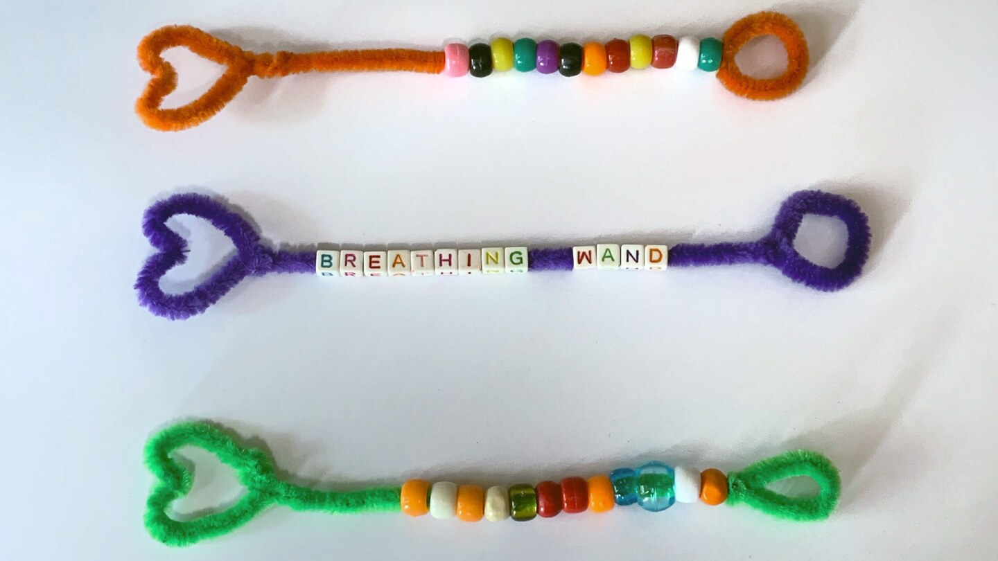 Three colorful pipe cleaners in the shape of wands with heart shapes on top threaded with beads.