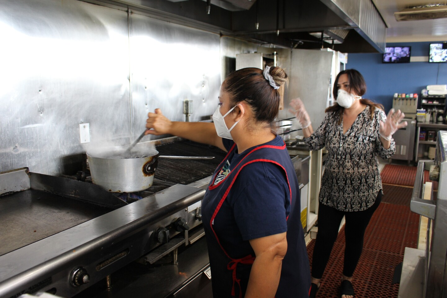 Janet, an employee at Aliki's Greek Taverna, stirs food for Fueling the Fearless