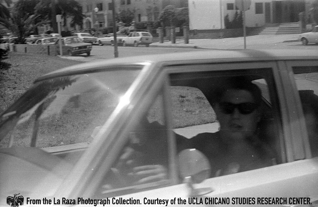 CSRC_LaRaza_B16F7S1_N021 LAPD officer in car during a Vietnam protest | La Raza photograph collection. Courtesy of UCLA Chicano Studies Research Center