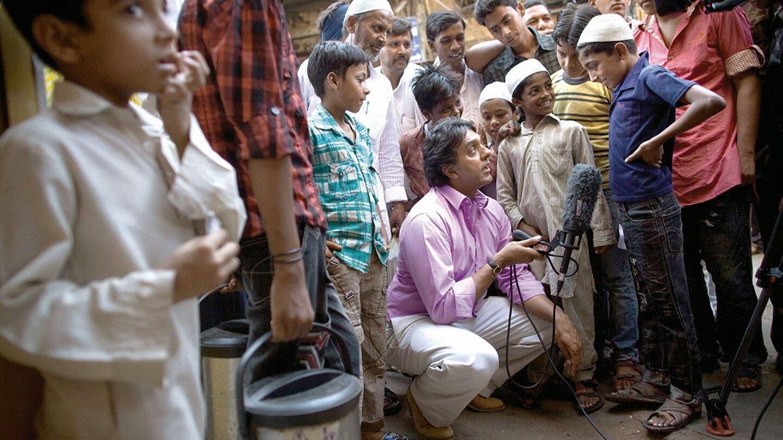Al Jazeera English News Bulletin reporter crouched down interviewing children.