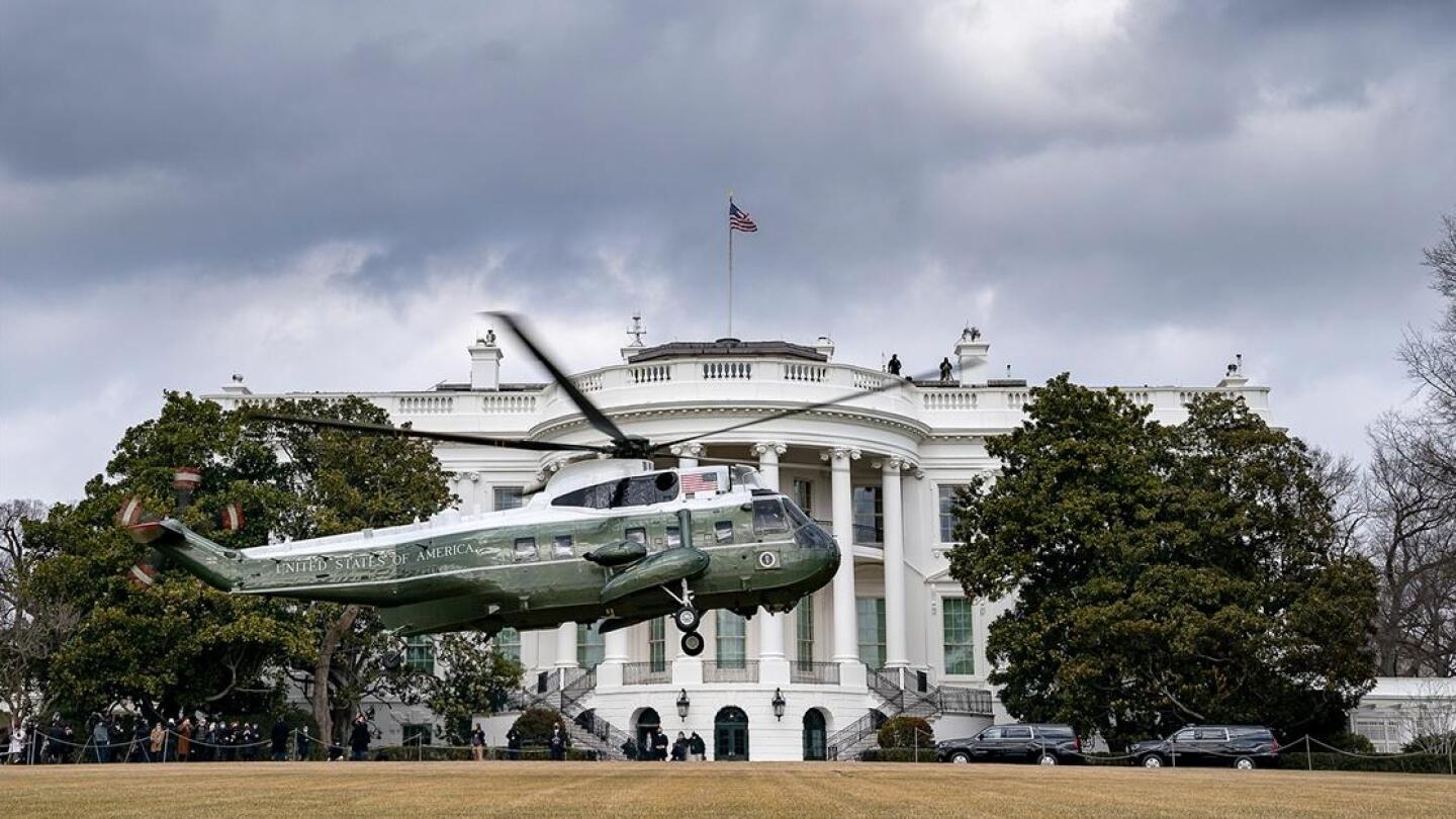 A helicopter landing in front of the White House.