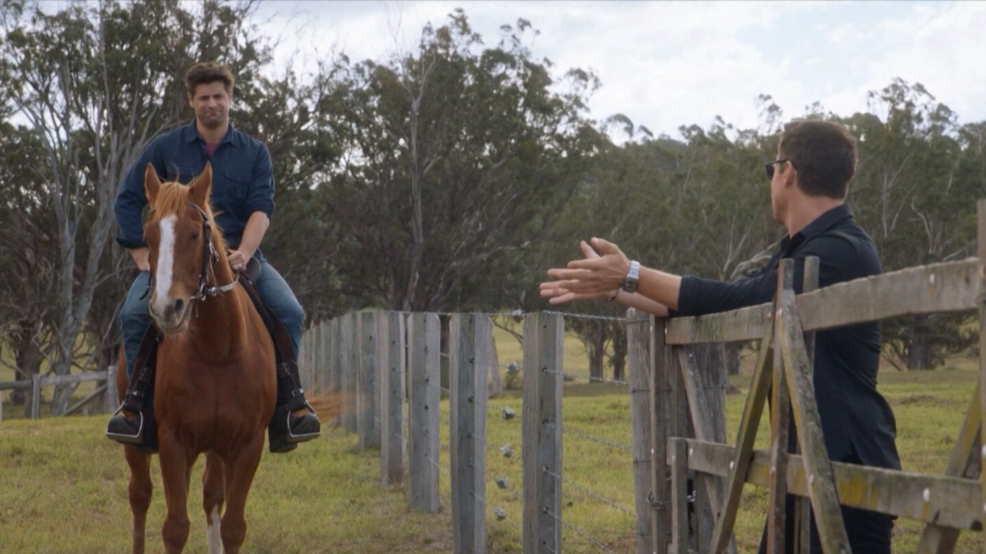 "A man rides a horse while another man leans on an adjacent fence. | From ""The Heart Guy: S3 E2"""