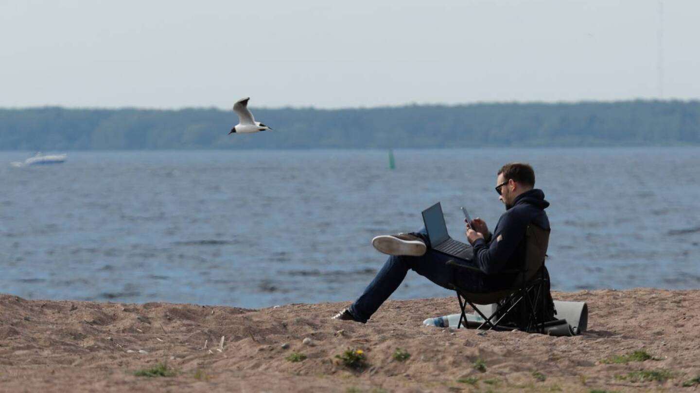 FILE PHOTO: A man uses his smartphone and laptop as he sits on the shore of the Gulf of Finland amid the outbreak of the coronavirus disease (COVID-19) in Saint Petersburg, Russia May 27, 2020.   REUTERS/Anton Vaganov