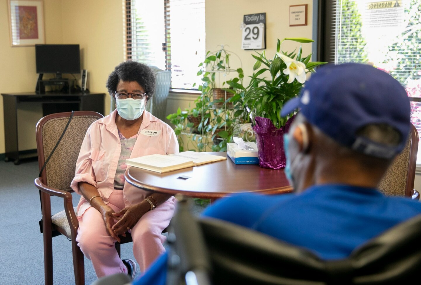 A Black woman wearing a face mask and a pink jacket and pants looks longingly at a man in a baseball cap sitting across her inside a nursing home.