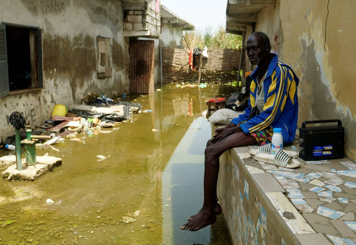 Issa Camara sits in the flooded alley of his home after heavy rains in Yeumbeul district on the outskirts of Dakar, Senegal, September 15, 2020. | REUTERS/Christophe Van Der Perre