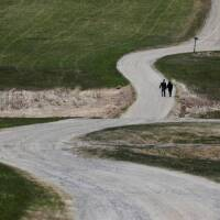 Two people walk along a gravel road amid the coronavirus disease (COVID-19) outbreak in Sabattus, Maine, U.S., April 25, 2020. | REUTERS/Brian Snyder