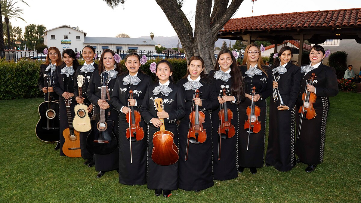Mariachi Conservatory All-Female Ensemble preparing to perform at the pre-concert outdoor community stage, including Angelica Mata (far left) and sister America (third from right) with their mom, Esperanza Juarez (far right). | Eddie Sakaki
