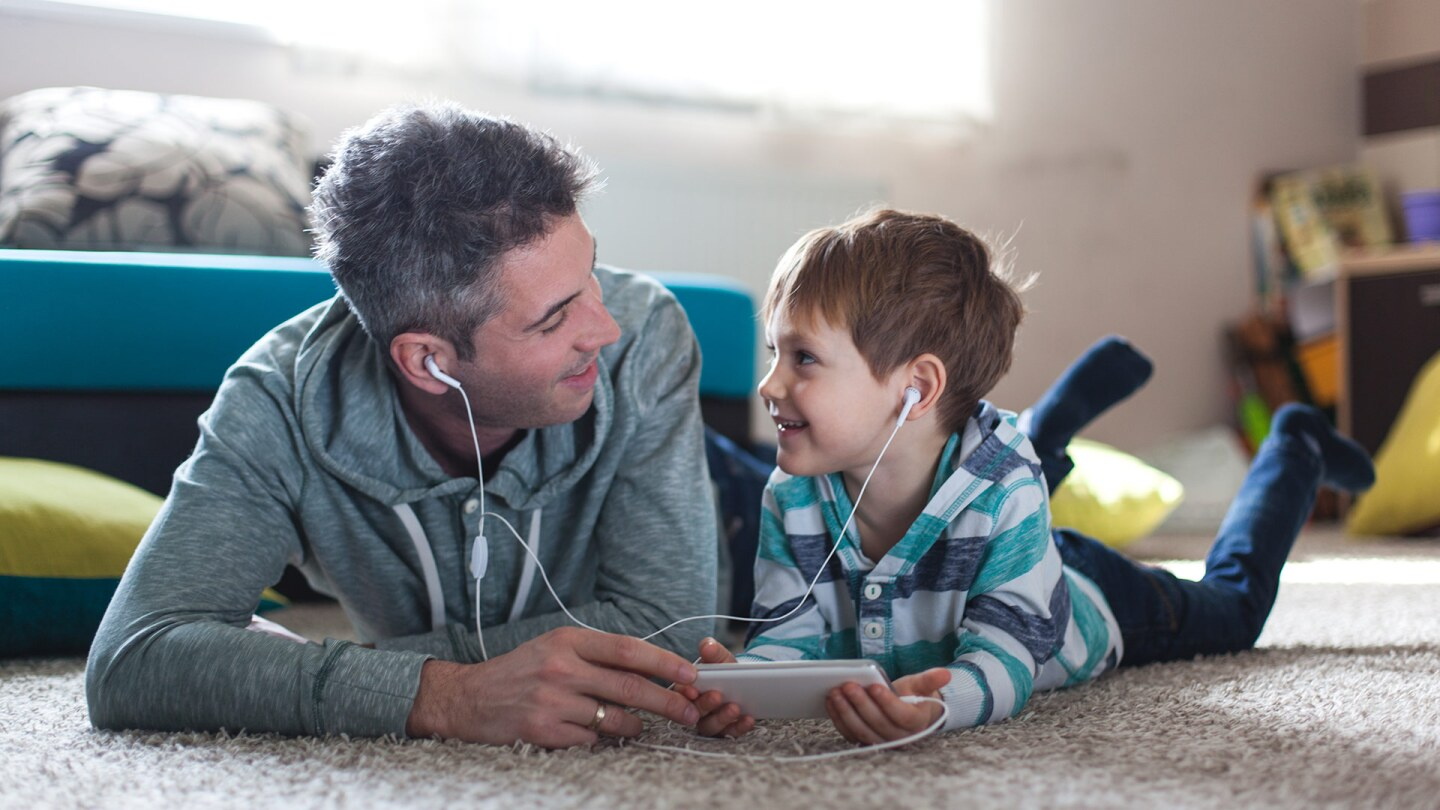A man and a little boy watch something on a tablet together as they lie down on a carpet next to each other