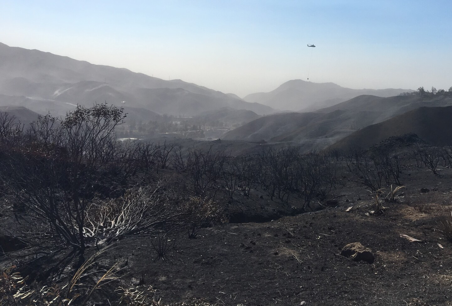 Scorched Hills in Malibu with helicopter carrying water in the distance during the Woolsey Fire